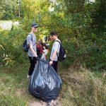 Dva žáci táhnou pytel s nalezeným odpadem